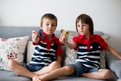 Crianças pequenas, irmãos do menino, jogando com rotação colorida da inquietação imagens de stock