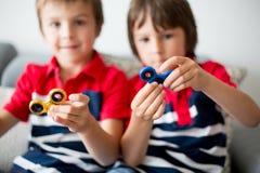 Crianças pequenas, irmãos do menino, jogando com rotação colorida da inquietação foto de stock royalty free