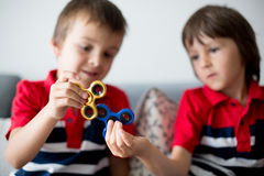 Crianças pequenas, irmãos do menino, jogando com rotação colorida da inquietação foto de stock