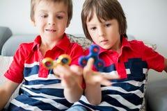 Crianças pequenas, irmãos do menino, jogando com rotação colorida da inquietação fotografia de stock royalty free