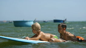 Crianças pequenas que apreciam as mãos surfboarding e de ondulação do mar no movimento lento vídeos de arquivo