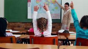 Crianças pequenas que escutam o professor que mostra o mapa na sala de aula filme