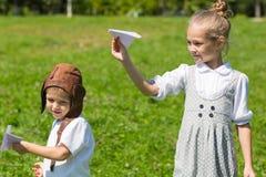 Crianças pequenas que jogam nos aviões de papel Imagem de Stock