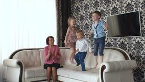 Crianças pequenas que saltam no sofá vídeos de arquivo
