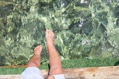 Crianças pequenas que sentam-se no cais de madeira na água e que apreciam o dia de verão Pés desencapados do menino Férias pelo m imagem de stock royalty free