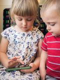 Crianças pequenas que usam o smartphone imagem de stock
