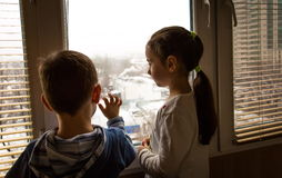 Crianças perto de uma janela Imagens de Stock