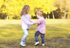 Crianças positivas felizes que têm o divertimento no dia do outono Fotos de Stock Royalty Free