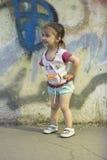 Crianças positivas A menina feliz 2-3-4 anos velha com as tranças em sua cabeça, está e sorri na rua perto de uma sagacidade do m imagens de stock royalty free