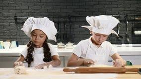 Crianças prées-escolar adoráveis que jogam a cozinha real dos cozinheiros chefe em privado Crianças nos aventais e nos chapéus br vídeos de arquivo