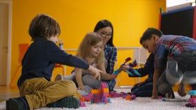 Crianças prées-escolar despreocupadas que relaxam na sala de jogos video estoque