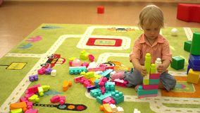 Crianças prées-escolar felizes que jogam com multi blocos coloridos no campo de jogos interno Atividade do esporte da criança video estoque
