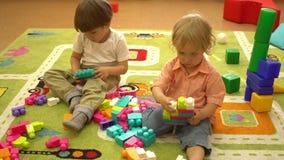 Crianças prées-escolar felizes que jogam com multi blocos coloridos no campo de jogos interno Educação no infantário video estoque