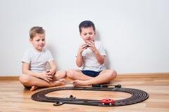 Crianças prées-escolar nos t-shirt brancos que jogam com uma trilha e os carros do brinquedo fotografia de stock royalty free