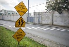 Crianças pretas e amarelas que cruzam adiante o sinal Imagem de Stock