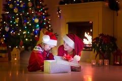 Crianças que abrem presentes de Natal na chaminé Fotos de Stock