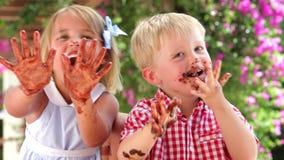 Crianças que acenam as mãos com cobertura em chocolate na câmera filme
