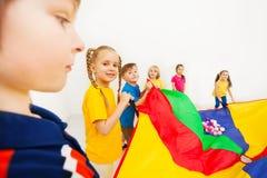 Crianças que acenam o paraquedas completamente de bolas coloridas Fotografia de Stock