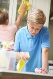 Crianças que ajudam com a cozinha das tarefas e da limpeza de agregado familiar Fotografia de Stock