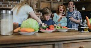 Crianças que ajudam pais com cozimento de vegetais do corte, família feliz que prepara o alimento junto na cozinha filme