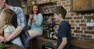 Crianças que ajudam pais com cozimento na cozinha, mãe feliz que olha o pai com as duas crianças que preparam o alimento em casa filme