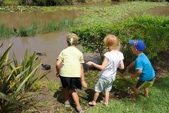 Crianças que alimentam patos na lagoa foto de stock
