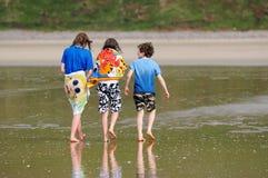 Crianças que andam ao longo da praia Imagem de Stock