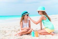 Crianças que aplicam o creme do sol entre si na praia O conceito da proteção da radiação ultravioleta fotografia de stock royalty free