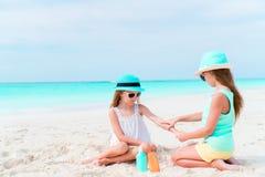 Crianças que aplicam o creme do sol entre si na praia O conceito da proteção da radiação ultravioleta foto de stock royalty free