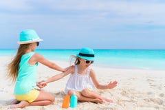 Crianças que aplicam o creme do sol entre si na praia O conceito da proteção da radiação ultravioleta foto de stock