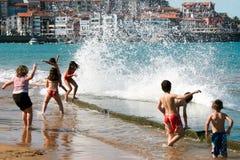Crianças que apreciam as ondas Fotografia de Stock Royalty Free