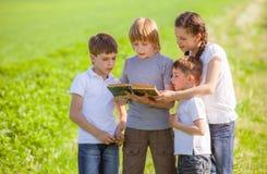 Crianças que apreciam a leitura Fotos de Stock