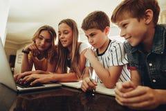 Crianças que aprendem junto em um portátil imagens de stock