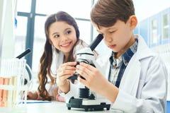 Crianças que aprendem a química em notas da experiência do microscópio do laboratório da escola imagem de stock royalty free