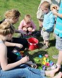 Crianças que atravessam seu ovo da páscoa Hunt Treas Imagens de Stock