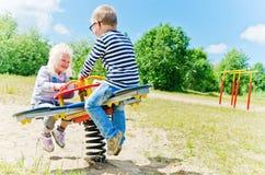 Crianças que balançam em um balanço Imagens de Stock