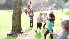Crianças que batem o Pinata na festa de anos no movimento lento