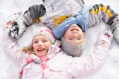 Crianças que colocam no anjo de factura à terra da neve Foto de Stock