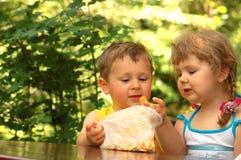Crianças que comem bolinhos fotografia de stock