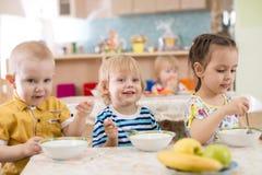 Crianças que comem no jardim de infância fotos de stock royalty free