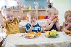 Crianças que comem no jardim de infância imagens de stock royalty free