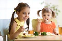 Crianças que comem o alimento saudável no berçário ou em casa imagens de stock