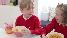 Crianças que comem o café da manhã junto antes de sair para a escola vídeos de arquivo