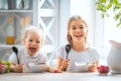 Crianças que comem o pequeno almoço imagem de stock