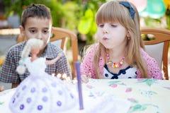 Crianças que comemoram a festa de anos e que fundem velas no bolo Fotos de Stock Royalty Free