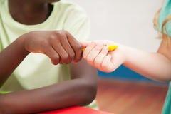 Crianças que compartilham de um lápis imagens de stock
