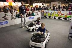 Crianças que conduzem carros bondes em G! vem o giocare em Milão, Itália Foto de Stock Royalty Free