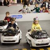 Crianças que conduzem carros bondes em G! vem o giocare em Milão, Itália Imagem de Stock