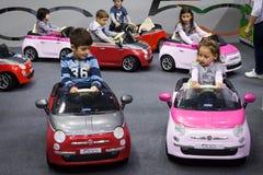 Crianças que conduzem carros bondes em G! vem o giocare em Milão, Itália Fotografia de Stock