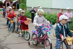 Crianças que conduzem em bicicletas e em 'trotinette's do desenhista em Rússia Fotografia de Stock Royalty Free